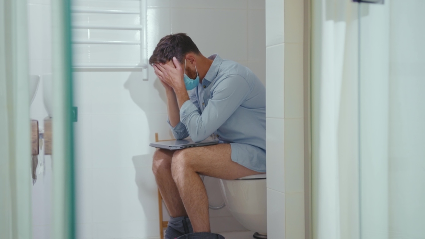 Unhappy worried businessman working on laptop wearing mask sit on the toilet at home restroom bearded wc isolation quarantine pandemic coronavirus covid-19 portrait close up slow motion | Shutterstock HD Video #1054675631