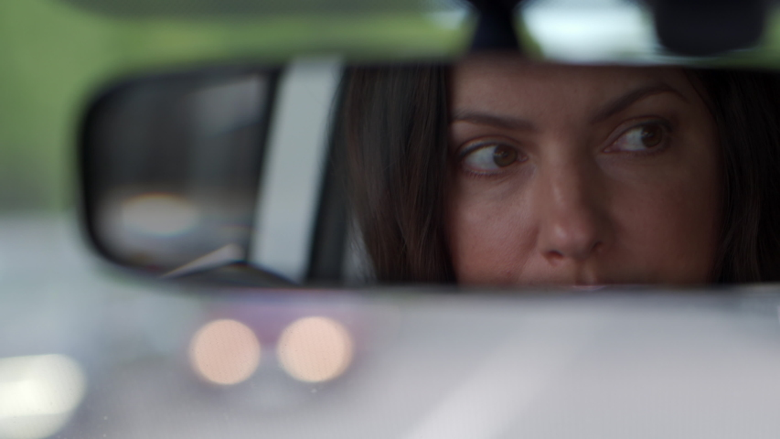 Beautiful brunette woman reflected in rearview mirror closeup, woman driving car, rear view of woman drives automobile through the city streets.