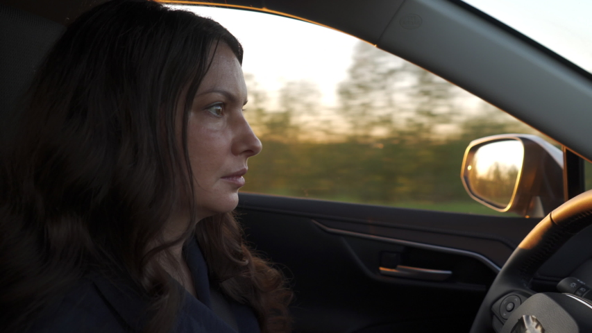 Beautiful brunette woman with long hair driving car at sunset adult woman driver drives automobile to destination close up.