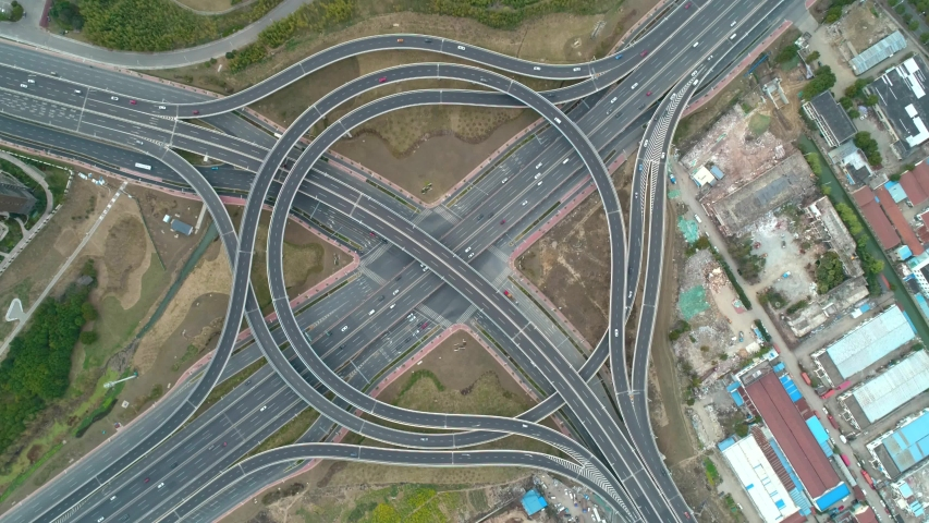 Top view to the cars driving on multi-level highway on the sunset. Highway multilevel junction road passing through the chinese city center. Highway overpass and junction with cars, trucks and buses. | Shutterstock HD Video #1054679162