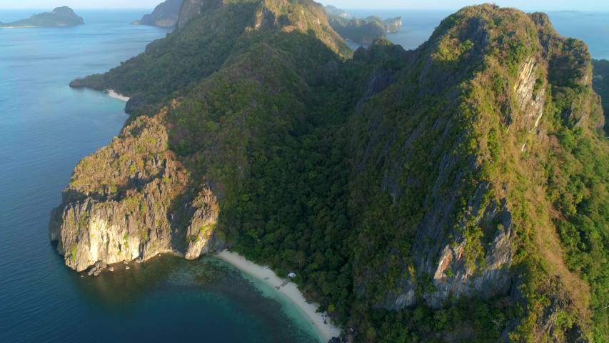 Aerial view of beach, sea and mountain in the sunset. El Nido, Palawan. Tropical landscape hill, mountains rocks with rainforest and azure water of lagoon.