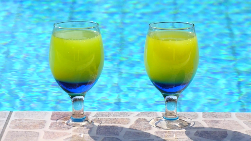 Two bright beautiful yellow-blue cocktails stand close-up on side pool, against background of pool, blue water. Summer pool party, poolside relaxation, vacation. Slow motion video. Vacation concept.   Shutterstock HD Video #1054680872