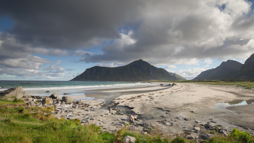 Back and forth film of clouds moving in the sky above the sandy beach and mountains, Lofoten, Norway | Shutterstock HD Video #1054681634