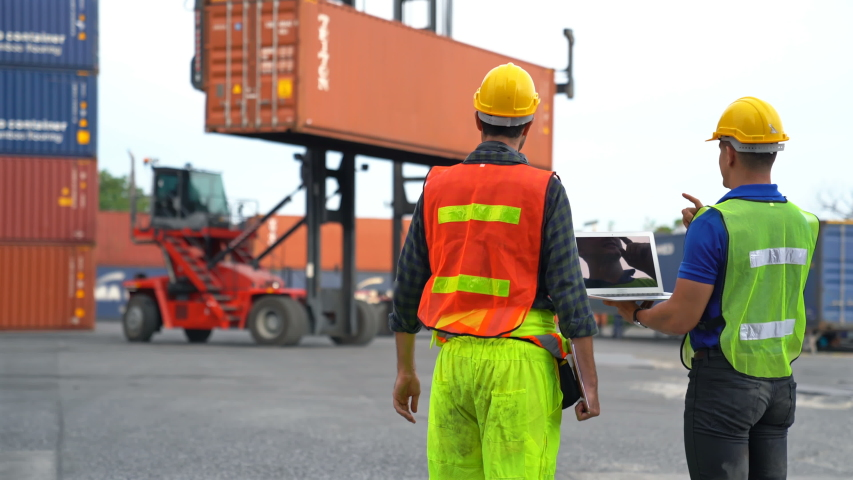 Engineer and foreman using laptop computer check Container loading real time monitoring system from cargo freight ship for import export. Logistic, Transportation concept.