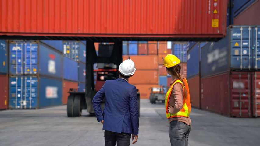 Engineer woman with Business man control loading Container from Cargo freight ship for import and export , support logistics transportation concept. | Shutterstock HD Video #1054681790