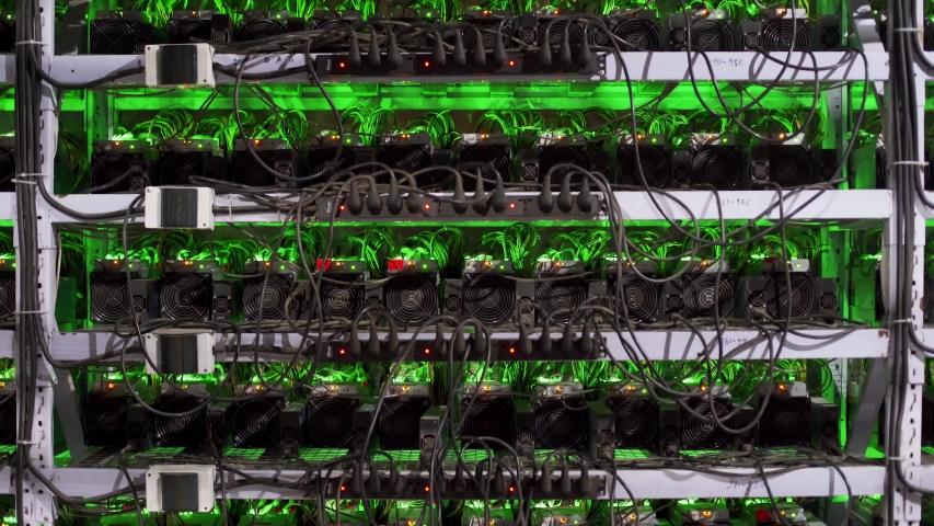 Large wired internet datacenter storage. ASIC miners on stand racks mine bitcoin in server room. Cryptocurrency mining equipment on large farm. Supercomputer blinking with lights. Defocus bokeh lights | Shutterstock HD Video #1054682060