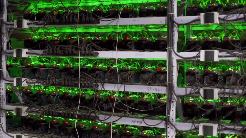 Cryptocurrency mining equipment on large farm. ASIC miners on stand racks mine bitcoin in server room. Blockchain techology application specific integrated circuit. Tripod panorama. | Shutterstock HD Video #1054682072