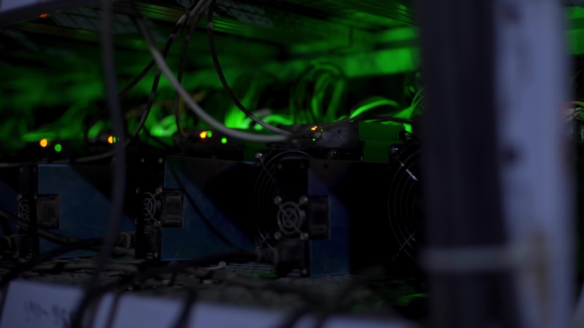 Large wired internet datacenter storage. Cryptocurrency mining equipment on large farm. ASIC miners on stand racks mine bitcoin in server room. Supercomputer blinking with lights. Light effects. | Shutterstock HD Video #1054682075