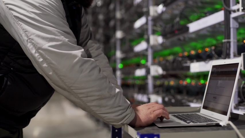 Data center diagnostics technician works and types on laptop. Mining equipment service in server room. Administrator repairs computing cluster with network hardware lights on background. Slider shot.