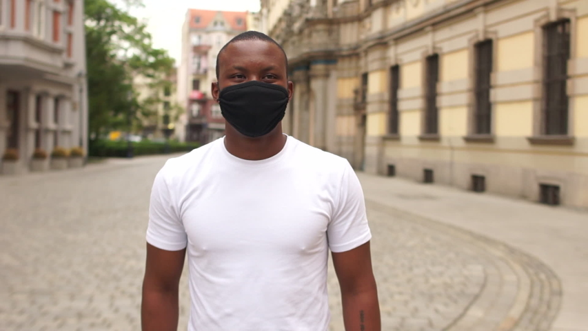Portrait of a young black man in a black mask on a city street. Protective mask after quarantine, post-quarantine life, new normality, black lives matter