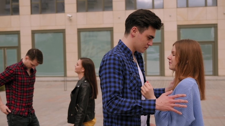 Funny friends are walking in the city in warm spring weather. Two couples of teenagers have fun and communicate in the city against the background of a modern building. | Shutterstock HD Video #1054683233