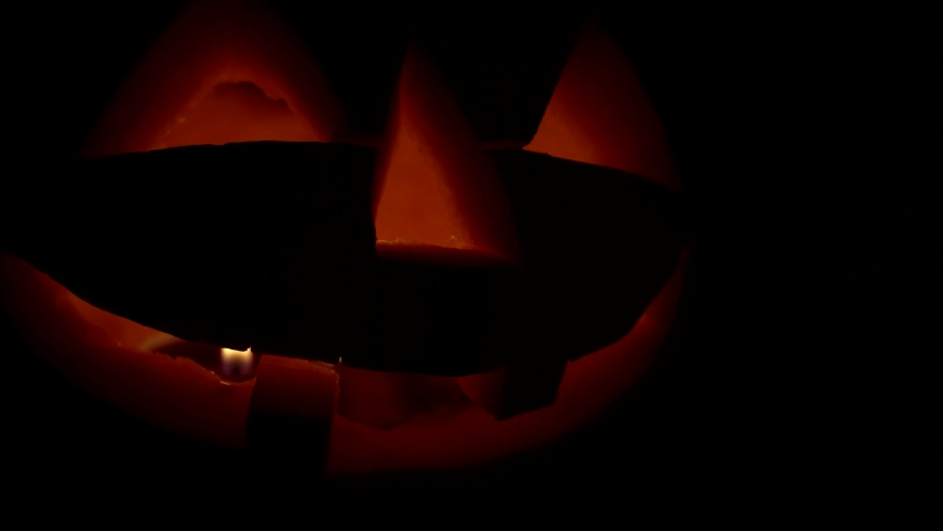A carved pumpkin for Halloween flickers in dark close-up, camera paning from right to left. Theme decorations for Halloween vegetables by hand made. Isolated fun pumpkin Jack face. | Shutterstock HD Video #1054685804