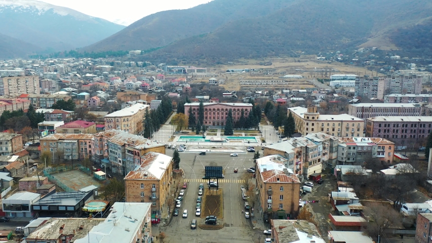 Top view city with mountains with tree in background. Aerial view square of  Vanadzor city, third-largest city in Armenia, Lori Province, Armenia. Drone's camera slowly move from square.