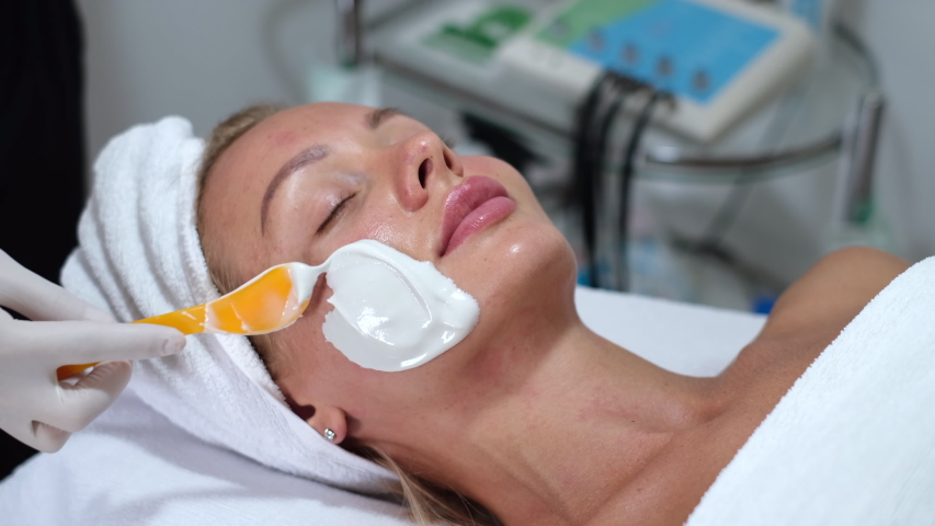 Cosmetologist applies alginate mask with spatula on face of woman. Facial skin and anti-aging treatment. Cosmetology and professional facial skin care.      | Shutterstock HD Video #1054692002
