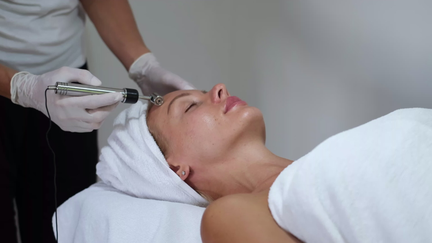Cosmetology. Woman in clinic receiving stimulating electric facial treatment. Closeup Of Young Female Face During Microcurrent Therapy.   | Shutterstock HD Video #1054692056