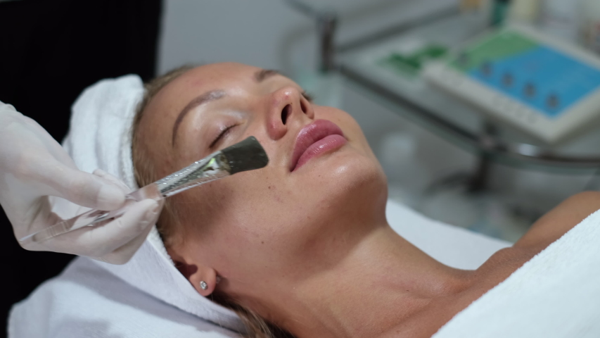 Cosmetologist apply clay mask with brush on young pretty woman face in beauty clinic, spa salon. Beautician making beauty facial skincare procedure to caucasian europian female   | Shutterstock HD Video #1054692080