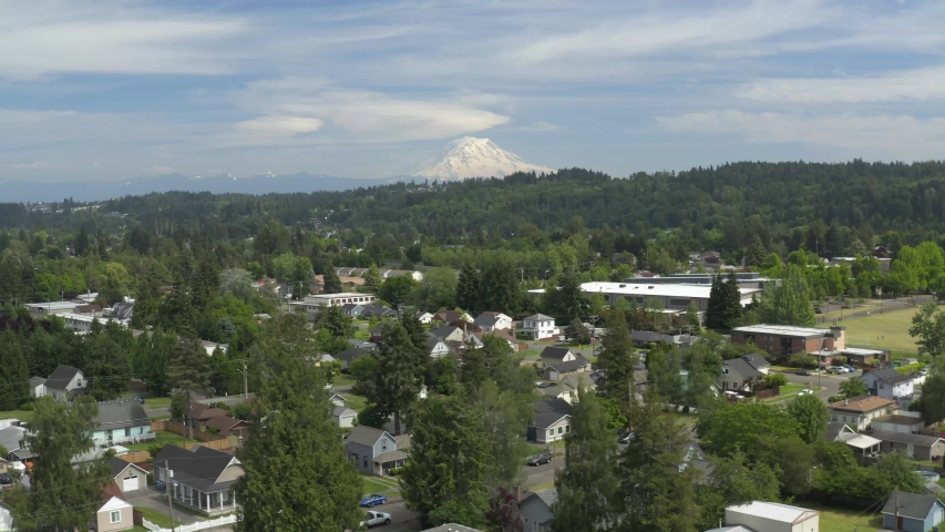 Rows Of Houses And Lush Trees In A Village In Puyallup, Washington With Snowy Mount Rainier In A Distance - aerial | Shutterstock HD Video #1054692497