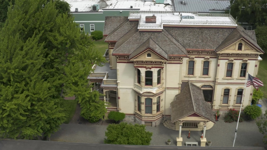 Historical Meeker Mansion With American Flag Waving On The Wind In Puyallup, Washington, USA. - aerial drone | Shutterstock HD Video #1054692566