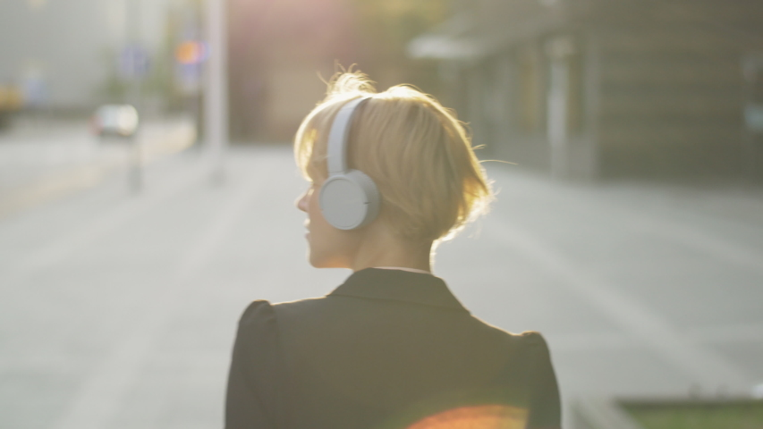 Female commuter with headphones walking on the street in the morning. Stylish woman listening to her favorite music track while getting ready for the start of a new day. Going to work. Royalty-Free Stock Footage #1054693142