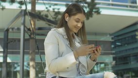 Young woman streaming music video clip online while sitting outside. Pretty female listening to music on earphones while looking at phone screen in the city. Fast wireless mobile internet.