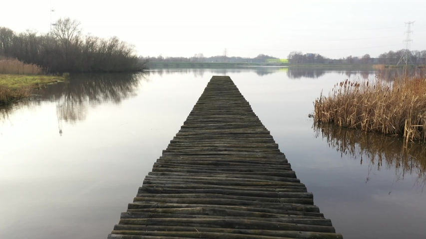 Slowly walking over a large wooden jetty into a lake and flying over the water afterwards Royalty-Free Stock Footage #1054693955