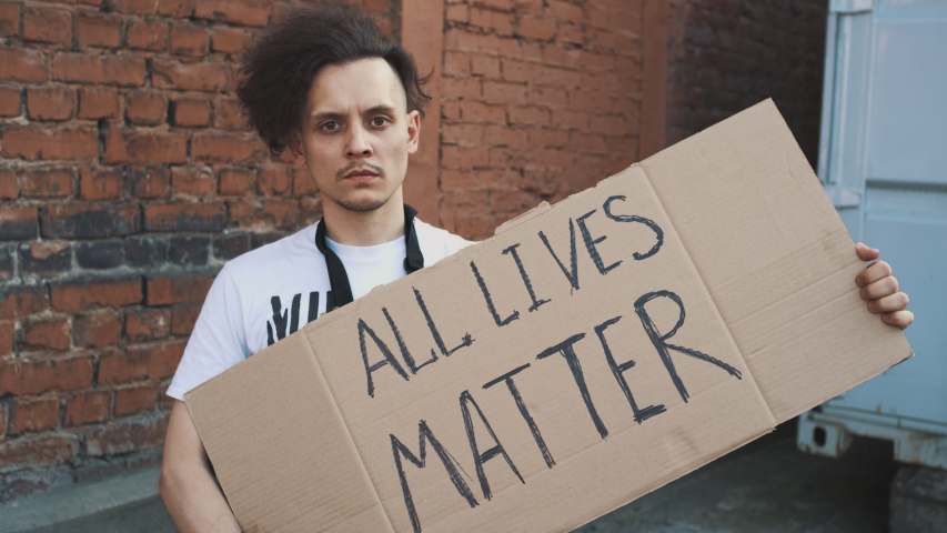 Caucasian man in mask stands against red wall with cardboard poster in hands with inscription - ALL LIVES MATTER. Single protest.