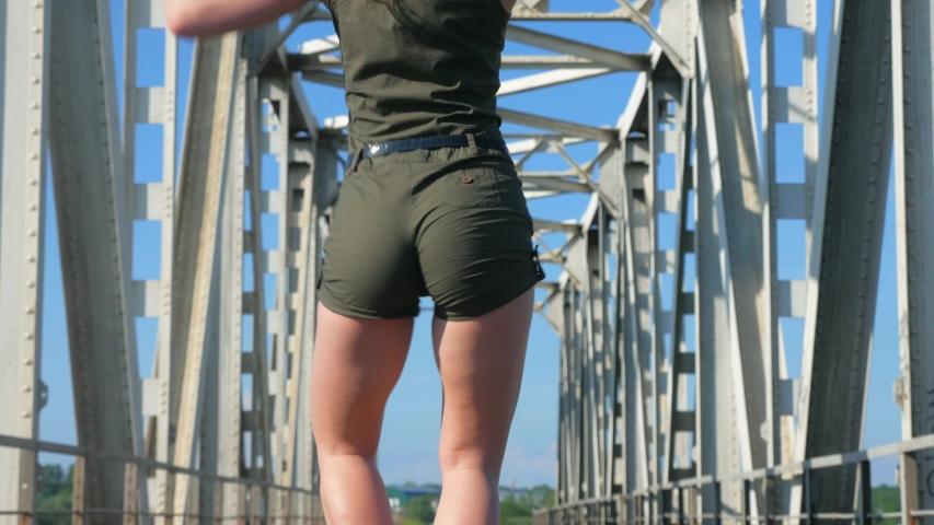 Sexy woman dancing on the railway bridge. Beautiful young dancer seductively dances and moves her buttocks. Girl dancing kizomba.