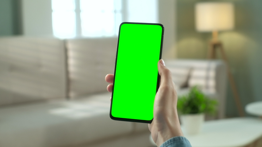 Point of View of Woman at Phone with Green Screen for Copy Space. Chromakey Mock Up Without Tracking Markers. 20s Lady Watching Video News on Couch Close up. Double Swipe Up