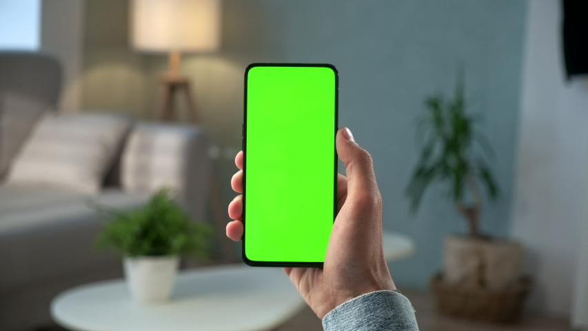 Handheld Camera: Point of View of Man at Modern Room Sitting on a Chair Using Phone With Green Mock-up Screen Chroma Key Surfing Internet Watching Content Videos Blogs Tapping on Center Screen