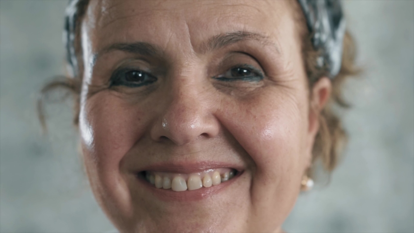 An happy old woman is smiling to camera. Close up shot of beauty elderly senior woman laughing | Shutterstock HD Video #1054696148