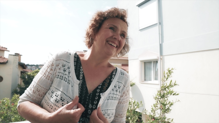 Happy old woman is smiling on balcony in sunny time. Elderly senior women, positive face concept.  | Shutterstock HD Video #1054696154