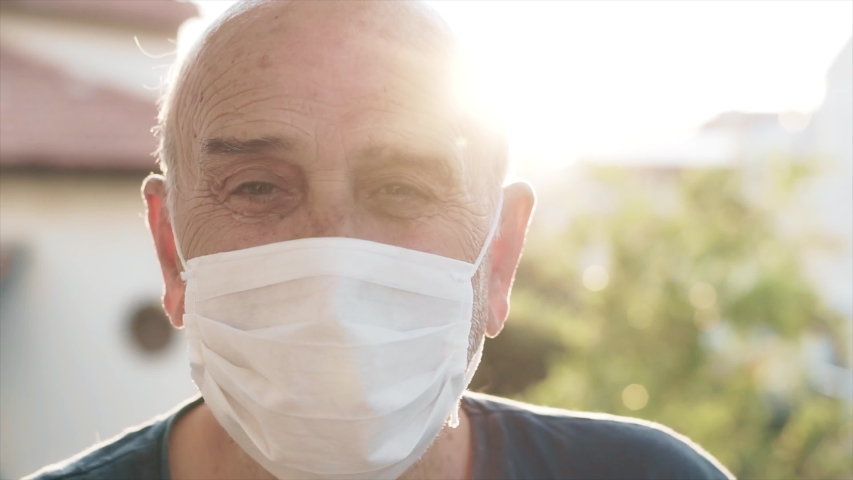 Senior old man is wearing face mask in outdoor. Sun light, flare and elderly senior guy is protecting himself from coronavirus, covid-19