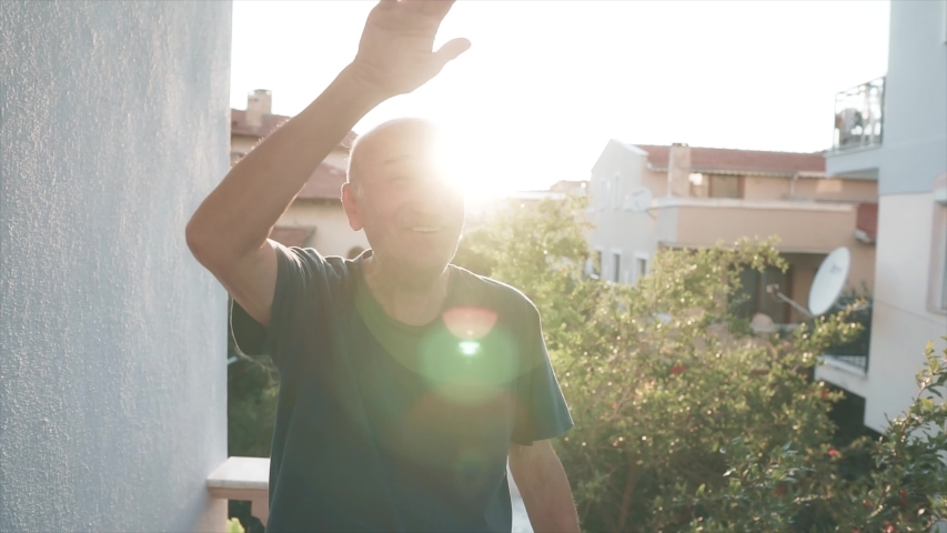Sympathetic old senior man is weaving on balcony. Happy, positive elderly person face with sun light, flare. | Shutterstock HD Video #1054696166