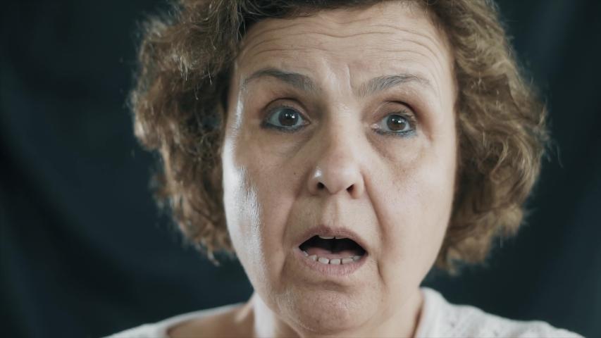 Old senior woman is shocked on black background. Elderly female is surprised. | Shutterstock HD Video #1054696196