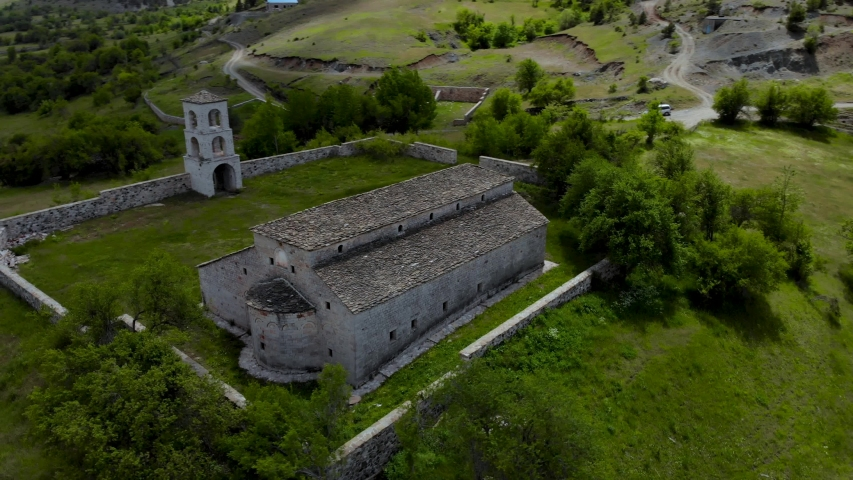 Church of Byzantine architecture built with caved stones on beautiful hill with green meadow and trees in Voskopoja, Albania