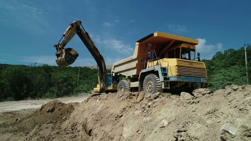 An Industrial Excavator On An Open Road Section Loads Rock And Earth On A Very Large Dump Truck, Loaded With Ore .The Excavator Bucket Drips And Loads The Ore.Panorama Of Construction Works.