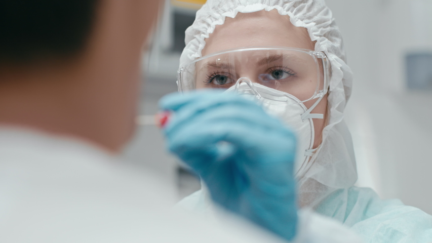 Hospital female employee at laboratory room closeup. Throat sample for corona virus test by medicine nurse in glasses indoors. Medical diagnostic equipment for coronavirus cure at modern doctor office Royalty-Free Stock Footage #1054697006