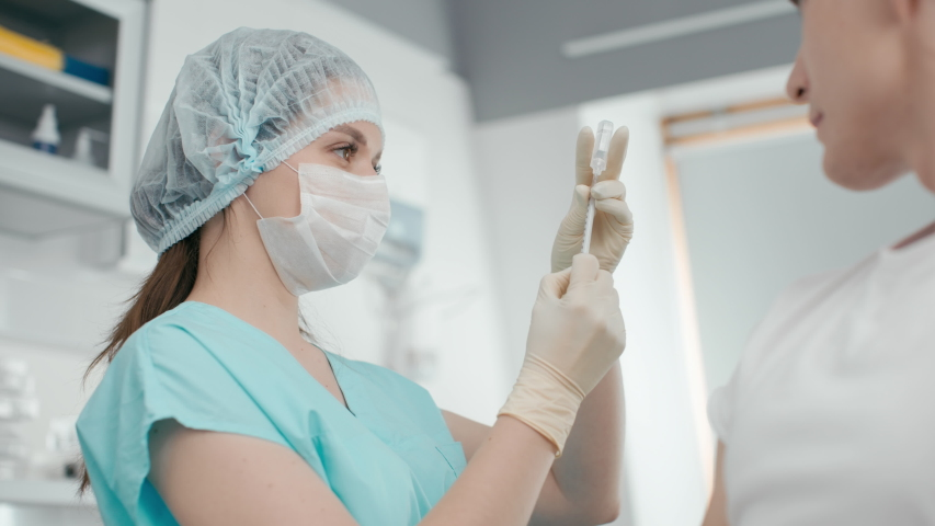 Hospital female employee at laboratory room close-up. Inject corona virus vaccine in hand by medicine nurse indoors. Medical shot of virology at covid-19 therapy at doctor office with modern equipment Royalty-Free Stock Footage #1054697015
