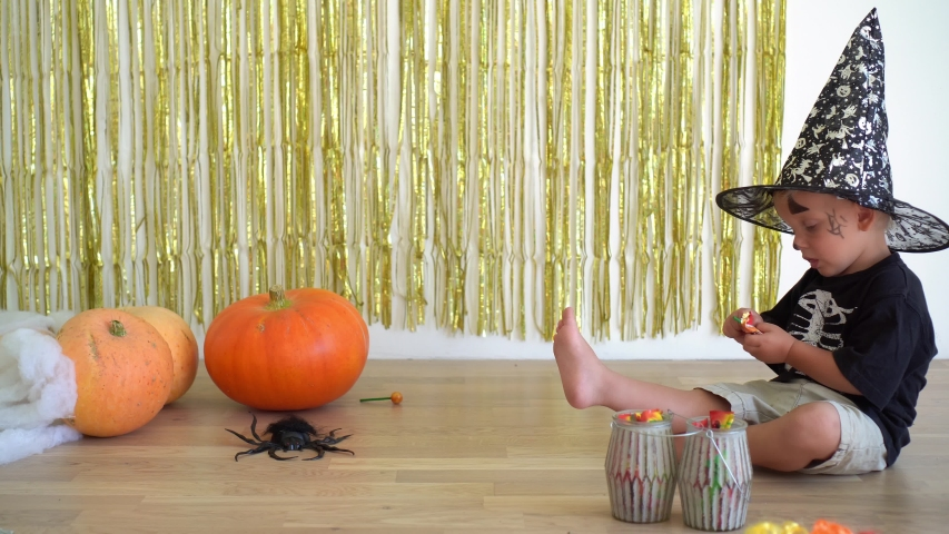 Cute 2 years old boy with magician wizard hat unpacking candy sweet sitting near pumpkins. Halloween celebration at home. Camera motion shot with gimbal. | Shutterstock HD Video #1054698062