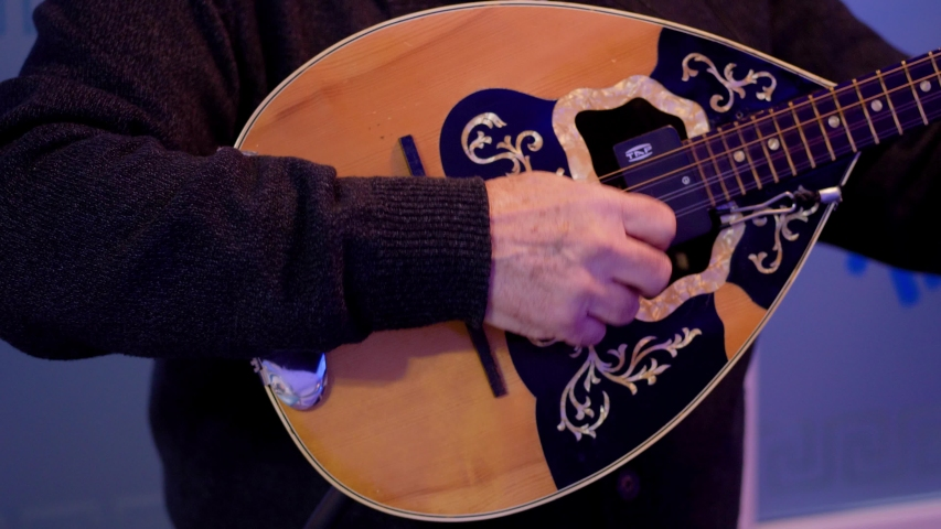 Fluent playing chords on a electrical mandoline closeup