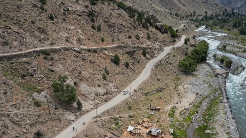 SUV on Curvy Road along Astore River in Valley, North Pakistan, Aerial