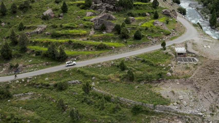 SUV driving along Astore Valley, Aerial Reveal River, North Pakistan