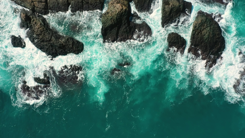 Aerial top view 4k footage by drone of ocean blue waves break on high cliff of a rocky mountain. Danger sea waves on a beach