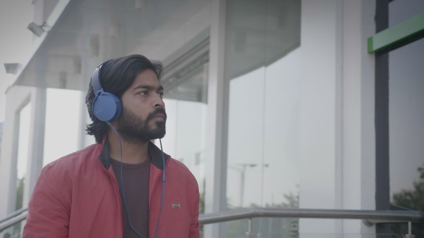 A movement shot of a young bearded man walking and dancing outdoors in the urban or city streets wearing headphones while listening or enjoying upbeat music on a smartphone or mobile phone | Shutterstock HD Video #1054699058