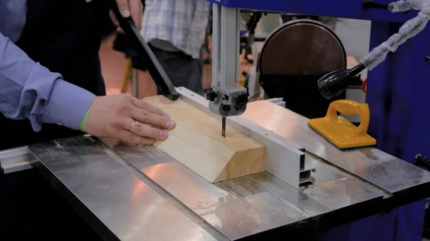 Professional man carpenter hands using electric bandsaw tool, cutting piece of wood at workshop - close up. Design, carpentry, equipment, craftsmanship, industrial, woodwork, manufacturing concept | Shutterstock HD Video #1054700927