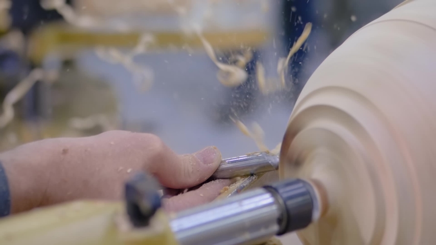 Super slow motion: professional man carpenter holding skew chisel, shaping piece of wood and using wood turning lathe at workshop - close up. Design, carpentry, craftsmanship, manufacturing concept | Shutterstock HD Video #1054700975