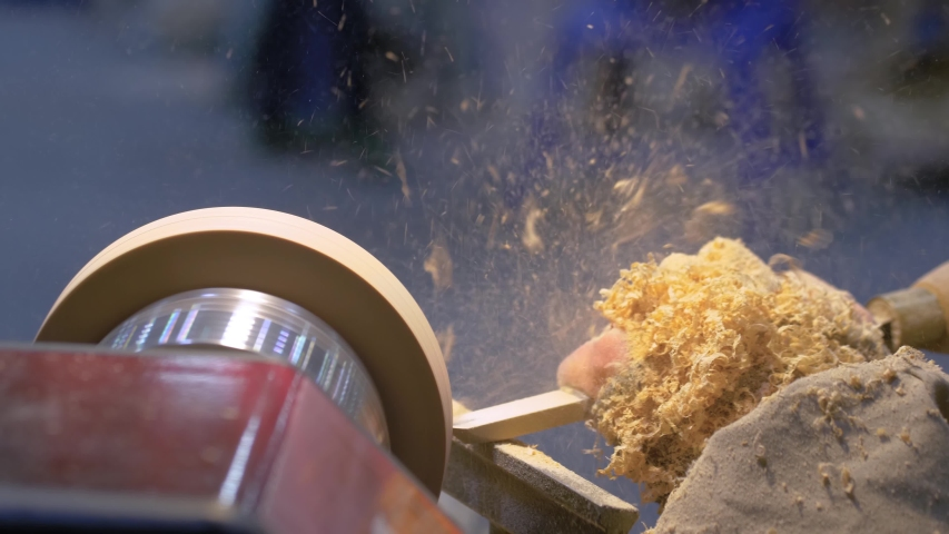 Carpentry, craftsmanship, design, manufacturing concept. Close up side view - professional man carpenter using skew chisel for shaping piece of wood on wood turning lathe at workshop - slow motion | Shutterstock HD Video #1054700978