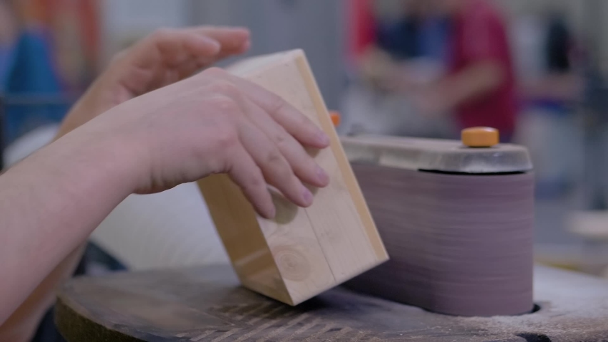 Super slow motion: professional man carpenter using belt sander machine, polishing wood product at workshop - close up. Design, handmade, woodwork, carpentry, craftsmanship, manufacturing concept | Shutterstock HD Video #1054700984