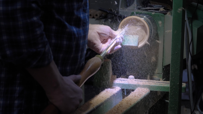 Slow motion: professional man carpenter hands using skew chisel for shaping piece of wood on wood turning lathe at workshop - close up view. Design, carpentry, craftsmanship, manufacturing concept | Shutterstock HD Video #1054700990