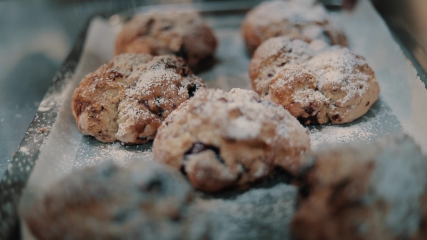 Dusting fruit scones on a tray with icing sugar through a sieve in slow motion. | Shutterstock HD Video #1054701200
